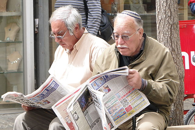 Two men reading the paper in Jerusalem. (We do not perform out-of-state moves)